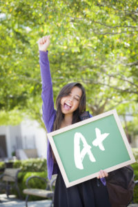 Excited Mixed Race Female Student Holding a Chalkboard With A+ Written on it.